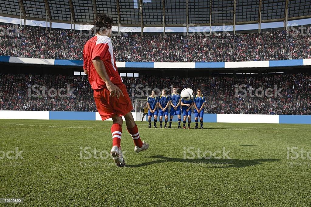 Footballer taking a free kick royalty-free stock photo