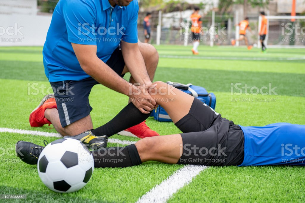 Footballer wearing a blue shirt, black pants injured in the lawn during the race. royalty-free stock photo