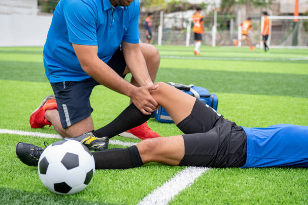 Footballer wearing a blue shirt, black pants injured in the lawn during the race. Footballer wearing a blue shirt, black pants injured in the lawn during the race. sport stock pictures, royalty-free photos & images