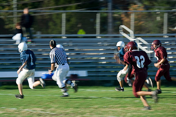 Footballs performing an American football game High school football players on the way to a first down. line of scrimmage stock pictures, royalty-free photos & images