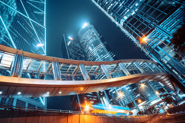 Footbridge and Corporate Buildings in central Hong Kong Footbridge and Modern office buildings in central Hong Kong at night elevated walkway stock pictures, royalty-free photos & images