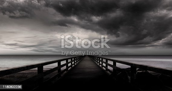 Footbridge into the water with storm clouds in stormy sea