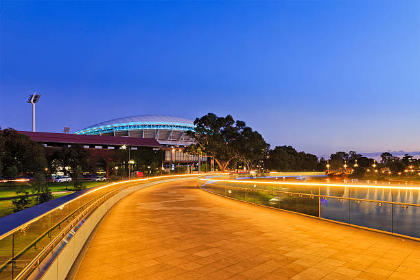 ADE Footbridge North width of modern footbridge over Torrens river in Adelaide, South Australia. Bright illumination lights reflecting in calm waters at sunrise footbridge stock pictures, royalty-free photos & images