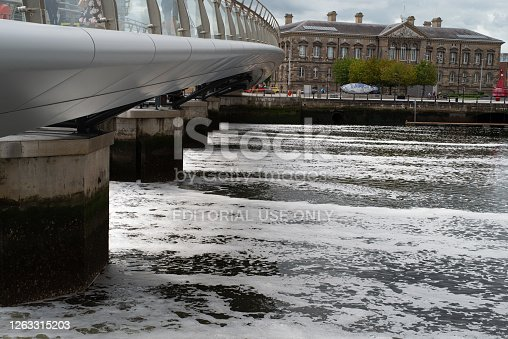 Belfast, Northern Ireland, UK - August 1, 2020:  Footbridge reaching over the River Lagan and its weir.  In the distance is the city's old Customs House.
