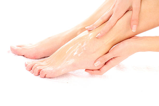 footcare (smearing cream) - human foot stock photos and pictures
