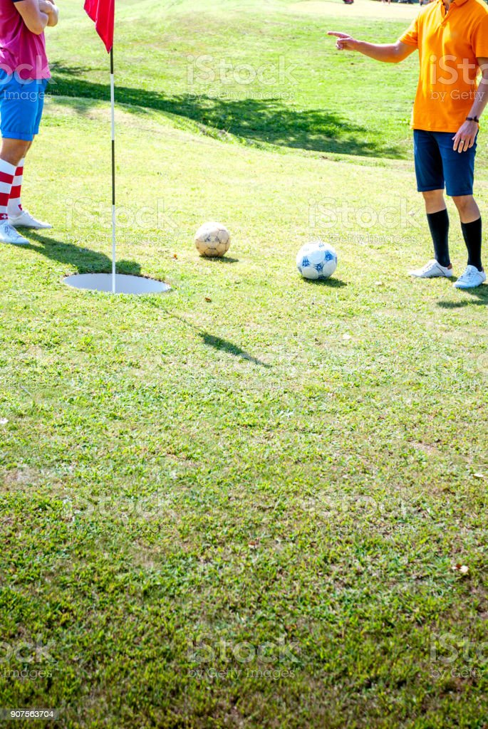 Footgolf Players Discussing Near the Hole stock photo