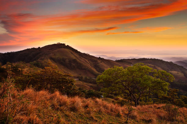 Foothills of Monteverde Cloud Forest Reserve, Costa Rica. Tropic mountains after sunset. Hills with beautiful orange sky with cloud. Evening landscape from Costa Rica. Mountain landscape from tropic stock photo