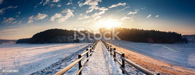 Snowy footpath by the frozen lake (Šmartinsko lake, Celje, Slovenia).