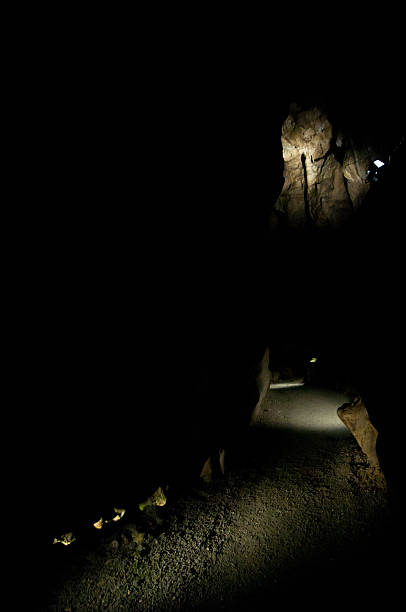 footpath in black cavern path spotlights in dark limestone, dripstone cave arcane stock pictures, royalty-free photos & images
