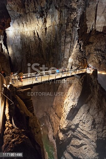 Skocjan, Slovenia: Tourists on underground bridge over of canyon inside a dark cave