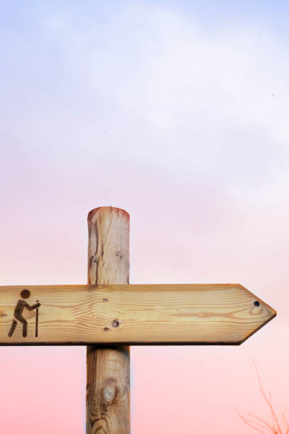 Footpath sign post, cloudscape sunset background. stock photo