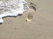 Footprint in the sand with the white foam of the waves.