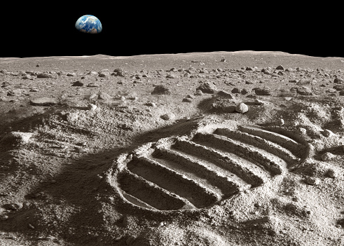 Footprint of astronaut on the moon with earth above the horizon. Photo of the earth has been used with courtesy of NASA database. Photo of the moon surface and the footprint has been created in the studio.