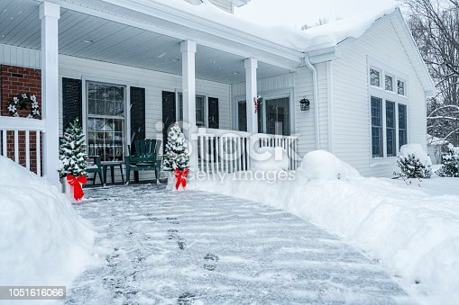 Deep snow has been shoveled, cleared and piled along the sides of the front yard footpath of this colonial style home. Two small holiday Christmas trees at the end of the walkway are decorated with Christmas ornaments and wide, bright red ribbon Christmas bows. Heavy blizzard snow continues to come down hard and blow around in all directions - already starting to re-coat the slippery surface and cover the fresh footprints. Nothing surprising here - just another early January winter snow storm in a rural suburban residential district neighborhood near Rochester, New York.