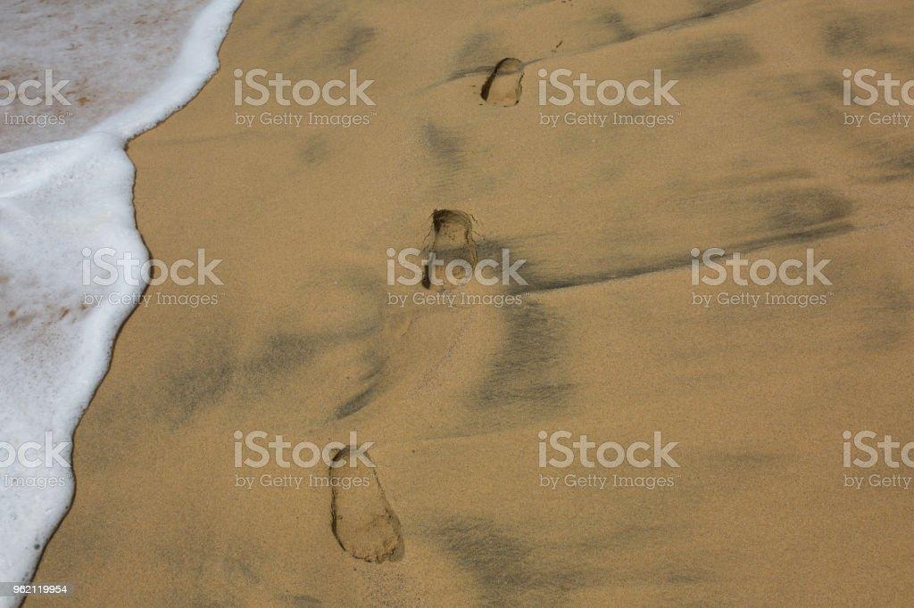 Footprints in sand beach near the edge of  splashing wave stock photo