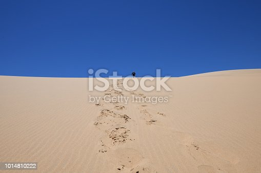 The sky is blue and the horizon bisects the photo. The footprints are in the centre of the photo leading to the silhouette climbing the dune.   The photo was taken at Sandwich Harbour in the permit only part of the Namib Naukluft Park, Namibia. The area can only be accessed by 4-wheel drive vehicles. The photo was taken in February 2018.