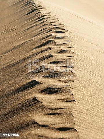 Trail of footprints in desert sand dune