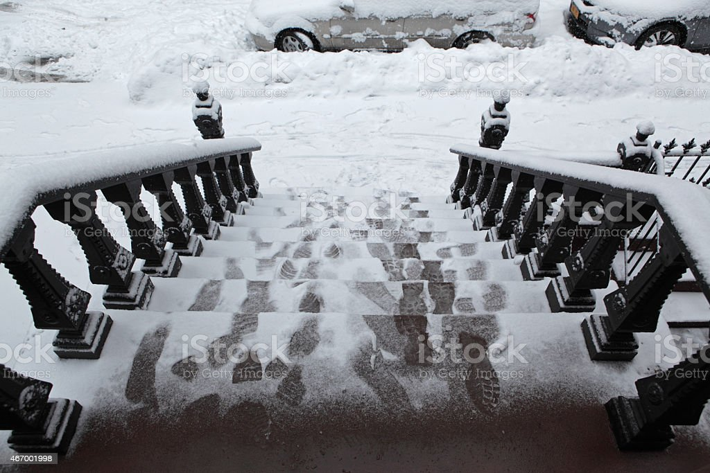 Footprints in snow on a  Brooklyn stoop in winter storm stock photo
