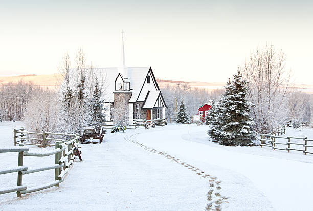 Footprints in snow to a charming country church in winter. stock photo