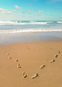 Footprints in the sand, heart shaped. Love traveling imprint on beach