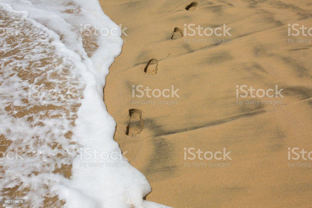 Footprints in the sand near coastline and splashing wave stock photo