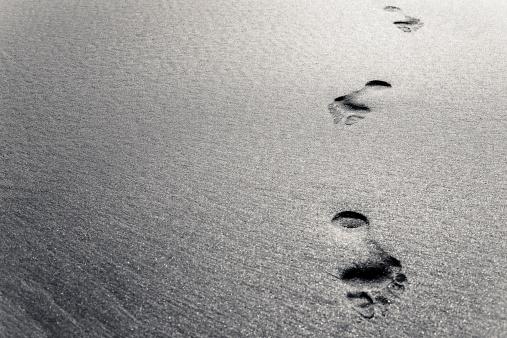 Footprints cross the sands. Colour toned.