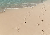 Footprints of bare feet are on a wet sand of the beach, summer vacation background photo