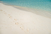 Sea water splashing sandy beach with footprints in it.