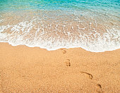 footprints on wet sand and beautiful turquoise water of mediterranean sea with soft white foam on sunny summer day in Spain