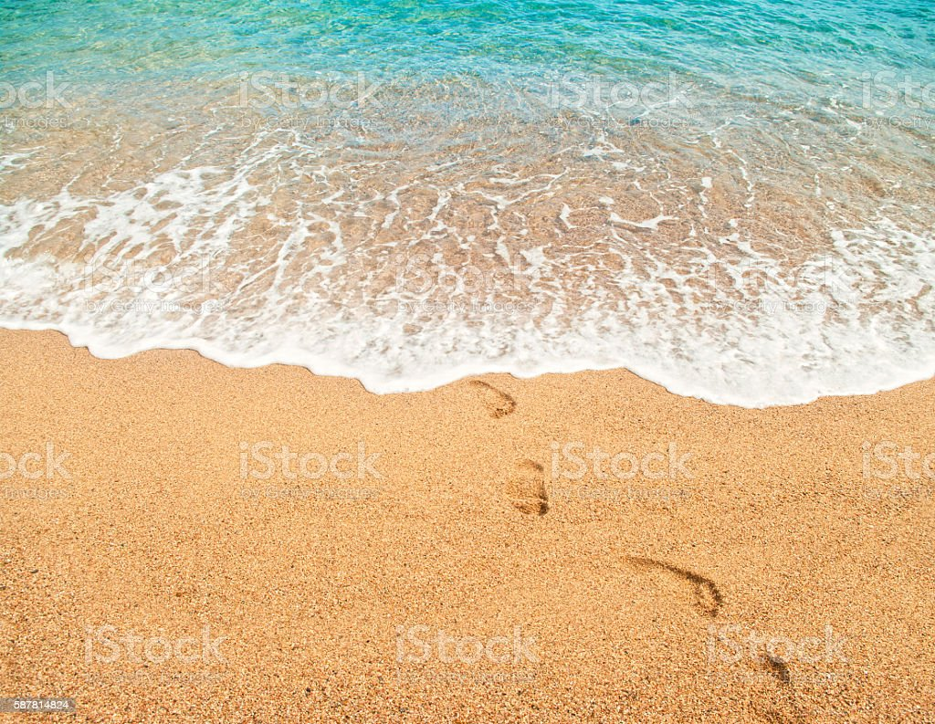 footprints on sand and turquoise sea water stock photo