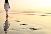 Rear view of young woman walking barefoot on wet shore at sunset. Female in sundress is leaving her footprints on sand. Low section of woman spending leisure time on idyllic beach.