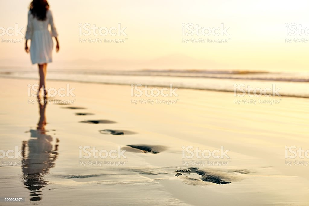 Footprints on shore with woman walking in distance at sunset stock photo