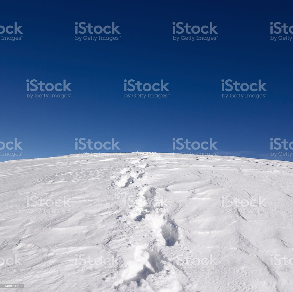 Footprints on snowy hill stock photo