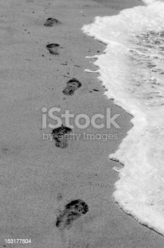 Footprints on the sand with white foam. Black and white picture