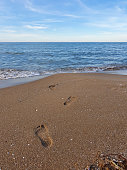 Three footprints on the sand, going towards a calm, blue sea with small waves.