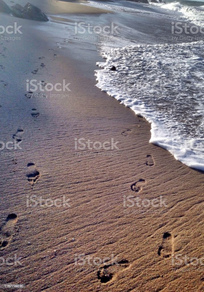 Footprints of a couple walking together on the beach's sand and the...