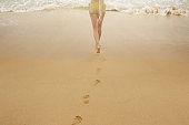 Female legs and footprints on the sand