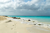 This tranquil beach scene was taken in Aruba.  The beach features white, sugary sand in the foreground and the turquoise Caribbean sea in the background.  Footprints in the sand help set the idyllic scene.