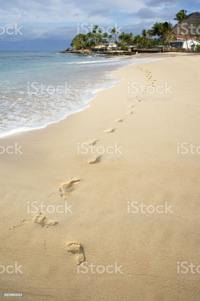 Footsteps in the sand on a beach in paradise. stock photo