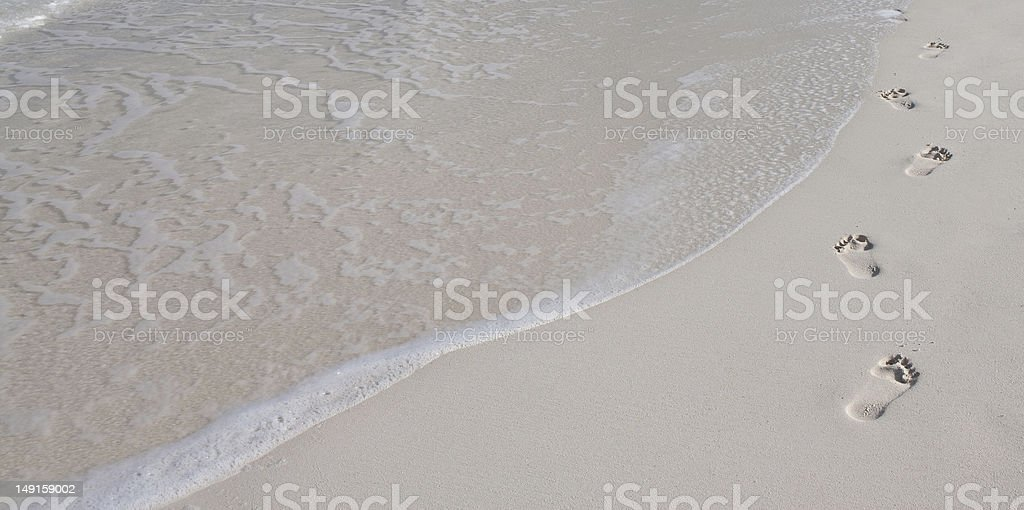 Footsteps in white sand stock photo