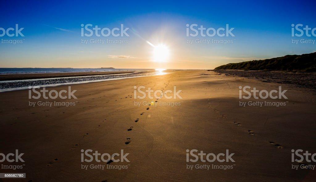 Footsteps on the shoreline at Bamburgh, Northumberland stock photo