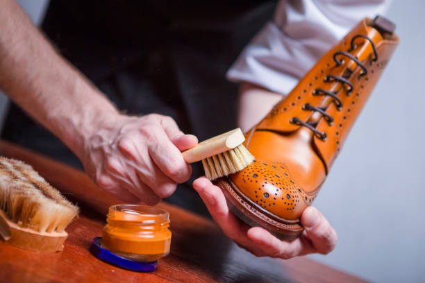 Footwear Care Ideas. Closeup of Mans Hands with Cleaning Brush Used for Polishing Tan High Derby Boots. Variety of Brushes Added. Horizontal Image Composition