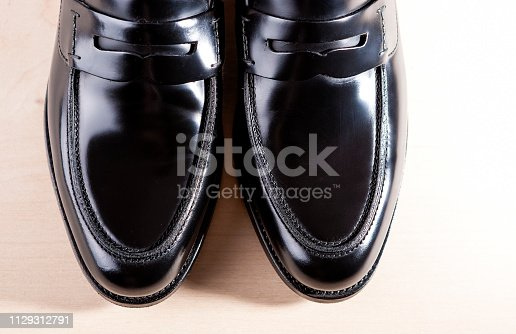 Footwear Concepts. Pair of Stylish Fashionable Real Leather Black Penny Loafers. Placed On Wooden Surface. Horizontal Image