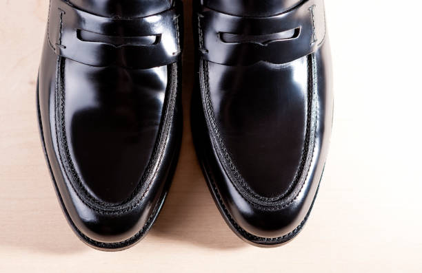Footwear Concepts. Pair of Stylish Fashionable Real Leather Black Penny Loafers.