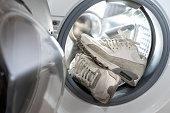 istock footwear hygiene - pair of dirty white sneakers in the washing machine 1277542999