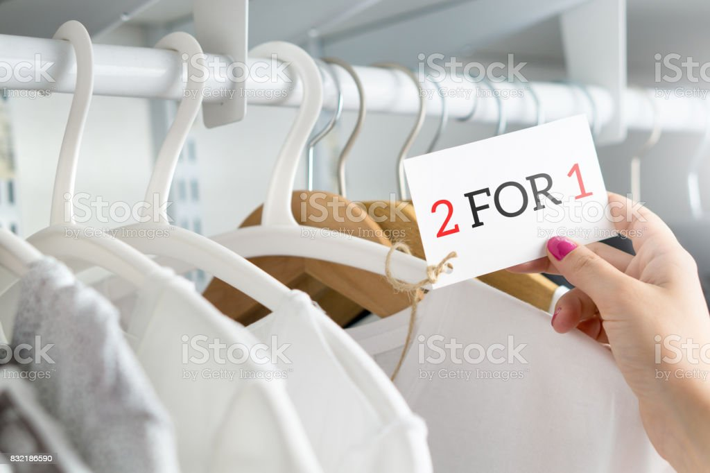 2 for 1 and two for one offer and special deal for t-shirt and clothing in clothes shop. Customer holding price tag with reduced discount price. Bargain and reduced cheap clothing in store. stock photo
