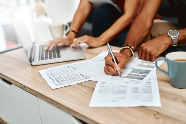 For a secure future you've got to plan for it Cropped shot of a couple going over their finances together at home plan document stock pictures, royalty-free photos & images