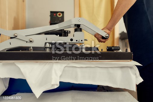 Cropped shot of male worker using heat press transfer machine for printing t-shirt. Printing on clothing and textiles concept. Horizontal shot. Side view
