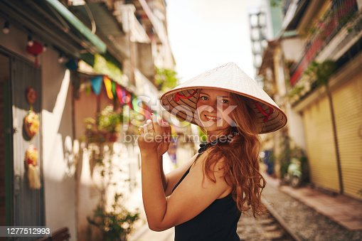Shot of a young woman wearing a conical hat while exploring a foreign city