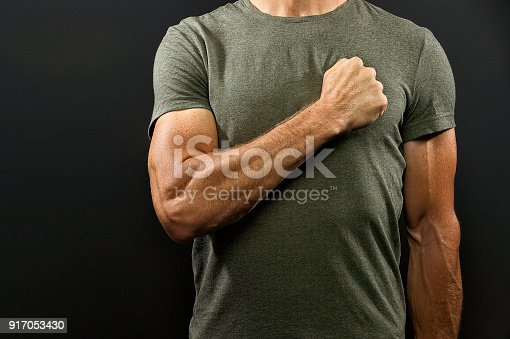 Portrait of a muscular Caucasian male holding his fist against his chest in a green t-shirt standing on attention against a Dark Background Cape Town South Africa